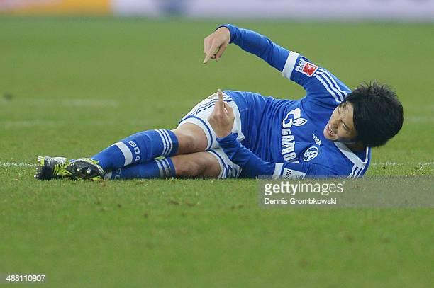 Atsuto Uchida of Schalke 04 reacts after suffering an injury during the Bundesliga match between FC Schalke 04 and Hannover 96 at VeltinsArena on...