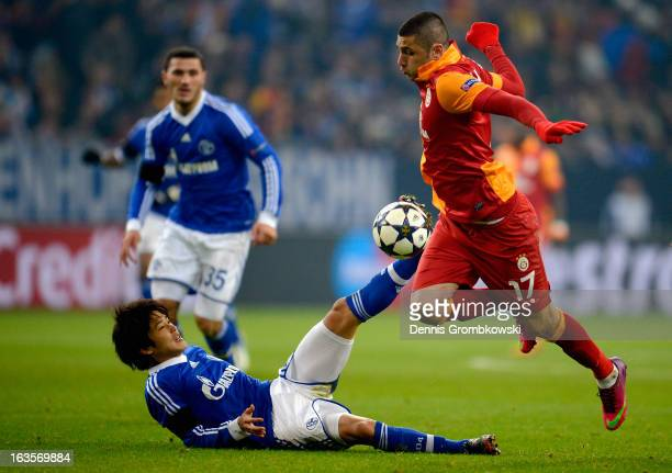 Atsuto Uchida of Schalke challenges Burak Yilmaz of Galatasaray during the UEFA Champions League round of 16 second leg match between Schalke 04 and...