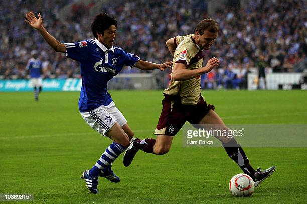 Atsuto Uchida of Schalke challenges Konstantin Rausch of Hannover during the Bundesliga match between FC Schalke 04 and Hannover 96 at Veltins Arena...