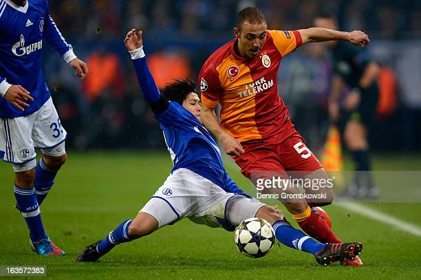 Atsuto Uchida of Schalke challenges Nordin Amrabat of Galatasaray during the UEFA Champions League round of 16 second leg match between Schalke 04...