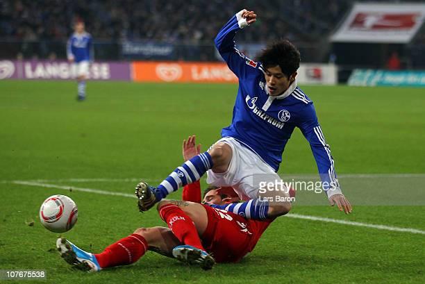 Atsuto Uchida of Schalke is challenged by Fabrice Ehret of Koeln during the Bundesliga match between FC Schalke 04 and 1 FC Koeln at Veltins Arena on...