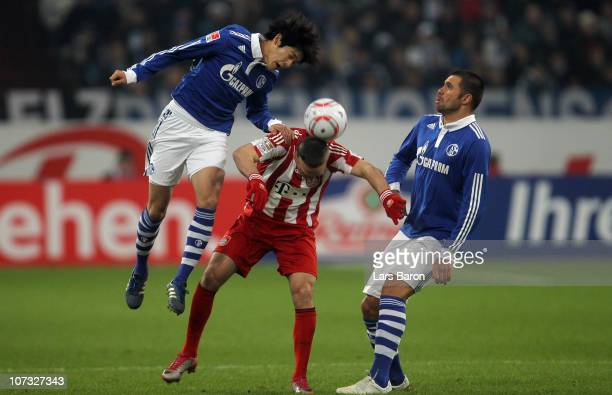 Atsuto Uchida of Schalke jumps for the ball next to Franck Ribery and team mate Edu during the Bundesliga match between FC Schalke 04 and FC Bayern...