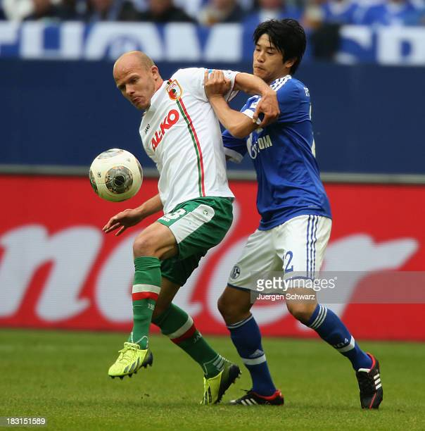 Atsuto Uchida of Schalke tackles Andre Hahn of Augsburg during the Bundesliga match between FC Schalke 04 and FC Augsburg at VeltinsArena on October...