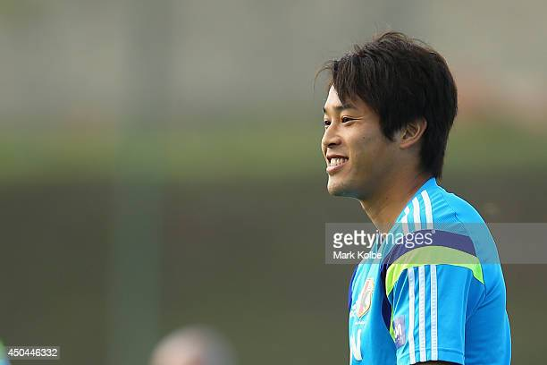 Atsuto Uchida smiles as he watches on during a Japan training session at the Japan national team base camp at the Spa Sport Resort on June 11 2014 in...