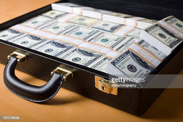 attache full of money on the table - money laundering stock photos and pictures