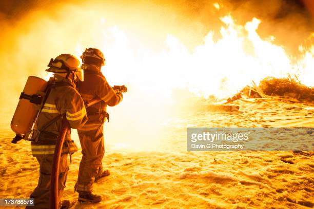 attacking the blaze - firefighter stock pictures, royalty-free photos & images