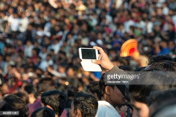 Attari, India - November 30 2013: A spectator takes picture by his mobile phone of crowds watching Attari - Wagah: India - Pakistan border closing...