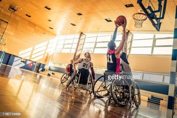 attempting a block during a wheelchair basketball game - persons with disabilities stock pictures, royalty-free photos & images