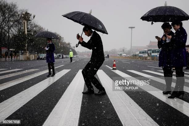 A attendant takes pictures of hostesses under the snow fall during the fifth plenary session of the first session of the 13th National People's...
