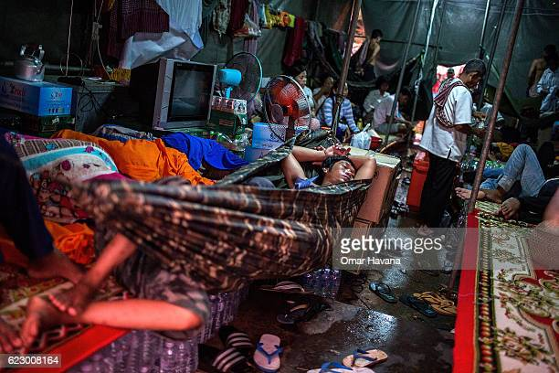 Attendants and crew rest inside a tent set up on the banks of the Tonle Sap River on the morning of the first day of the Water Festival on November...