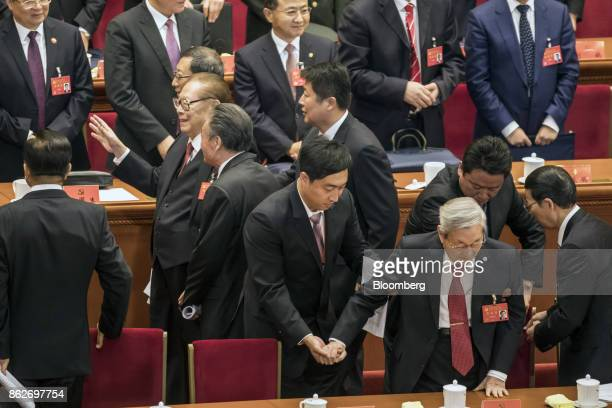 Attendants assist Zhu Rongji, China's former premier, front row third right, from his seat as Jiang Zemin, China's former president, second left,...