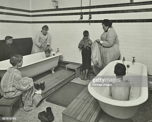 Attendants bathing boys at the Sun Court Cleansing Station City of London 1914 Sombre scene of women and boys in a tiled bathroom At this time many...