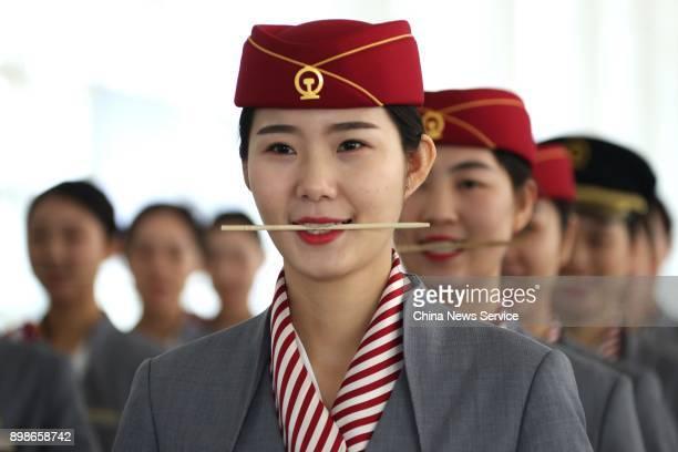 Attendants biting chopsticks practise smiling at Nanchang railroad section on December 25 2017 in Nanchang Jiangxi Province of China Train attendants...