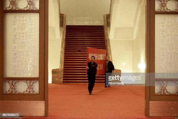 Attendants carry a banner through a hallway in the Great Hall of the People during the 19th National Congress of the Communist Party of China in...