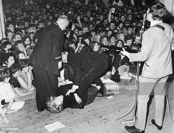 Attendants carry a young woman off stage who fainted while watching John Lennon sing A note to John Lennon asks him to sing her favorite song lays on...