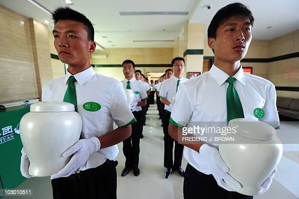 Attendants carry biodegradable urns at a cemetery in Tianjin northern China for a collective ecoburial on July 20 2010 In a country with 10 million...