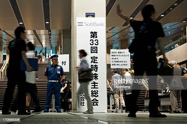 Attendants direct attendees arriving for the SoftBank Corp annual general meeting as a security officer stands guard in Tokyo Japan on Friday June 21...