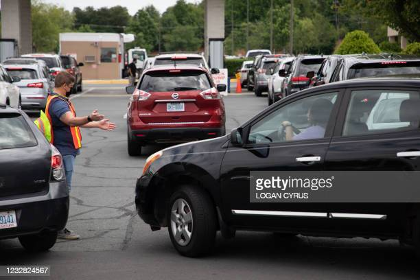 Attendants direct cars as they line up to fill their gas tanks at a COSTCO on Tyvola Road in Charlotte, North Carolina on May 11, 2021. - Fears the...