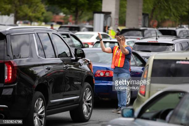 Attendants direct cars to gas pumps as they queue to fill their gas tanks at a Costco of Tyvola Road in Charlotte, North Carolina on May 11, 2021...