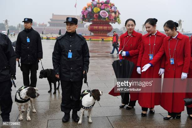 Attendants look at sniffer dogs while posing for photos in Tiananmen Square during the opening ceremony of the 19th Communist Party Congress in...