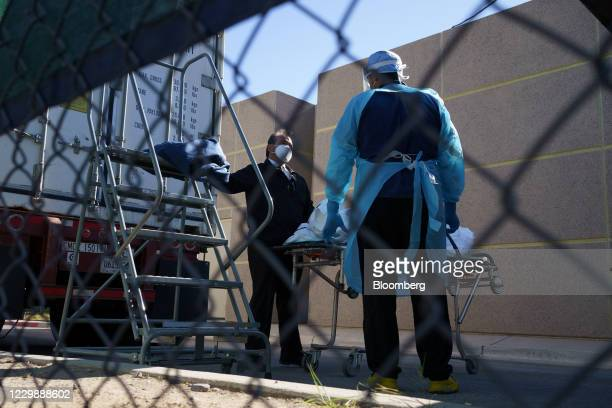 Attendants prepare to transport a body bag at the mobile morgue outside the Medical Examiners Office in El Paso, Texas, U.S., on Monday, Nov. 30,...