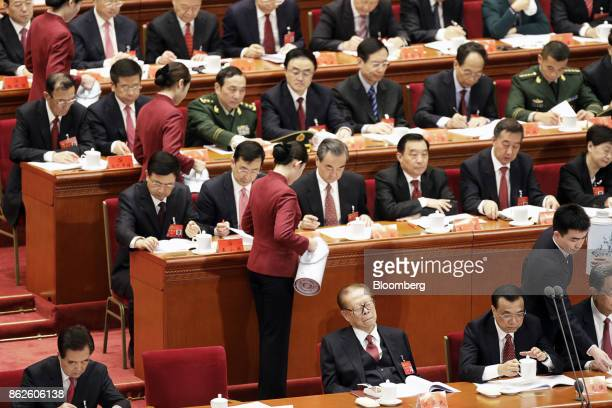 Attendants refill delegate's cups as Jiang Zemin, China's former president, bottom center, sits with eyes closed next to Li Keqiang, China's premier,...