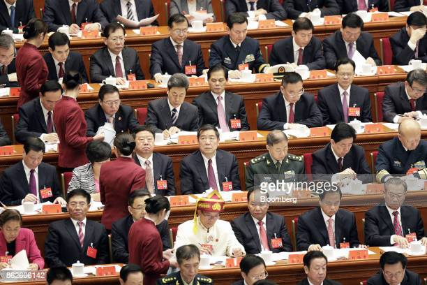 Attendants refill delegate's cups during the opening of the 19th National Congress of the Communist Party of China at the Great Hall of the People in...