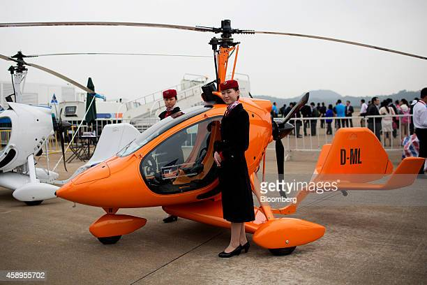 Attendants stand next to a Rotortec Cloud Dancer II gyrocopter manufactured by Rotortec GmbH during the China International Aviation Aerospace...
