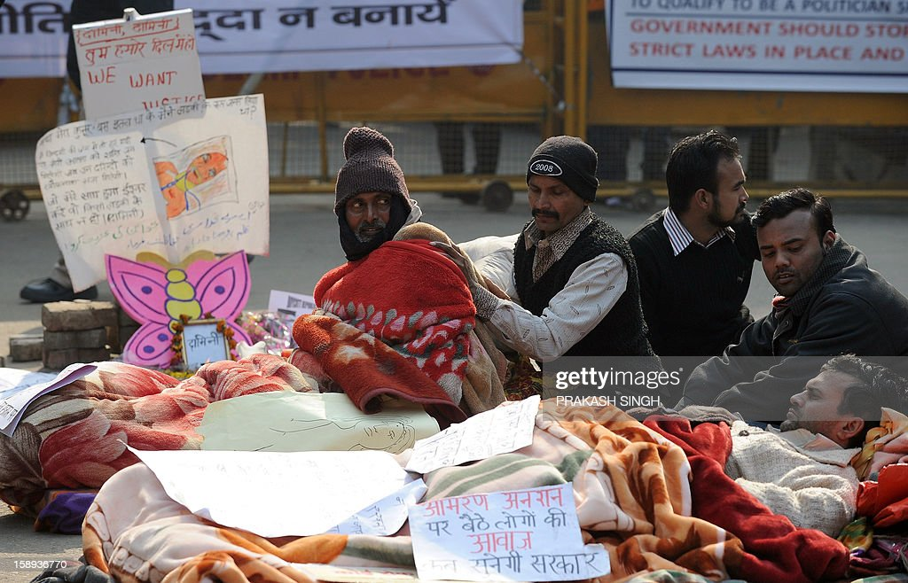 Attendants take care of hunger strikers (L and bottom) holding a fast following the death of a gang rape victim, in New Delhi on January 4, 2013. The brutal gang-rape of the 23-year-old medical student in New Delhi on December 16 has led to a bout of national soul-searching over the treatment of women in Indian society and provoked daily protests. AFP PHOTO/ Prakash SINGH