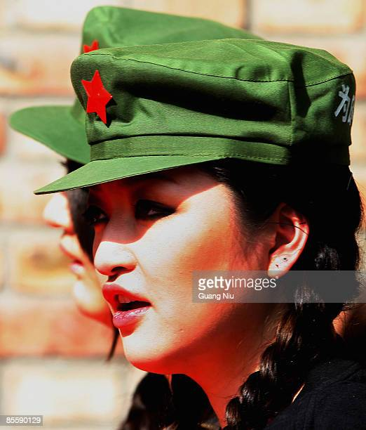 Attendants wear Chinese People's Liberation Army soldiers' old uniform to attract attention during the JudyGalaxy Fashion Collection at the China...