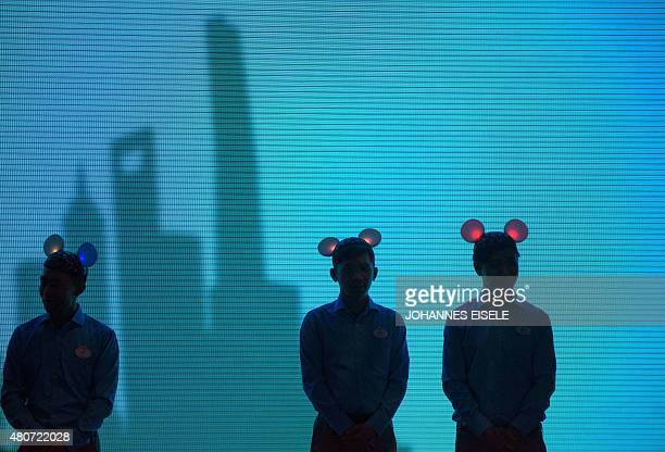 Attendants wearing Mickey Mouse ears stand in front of a large screen showing a picture of Shanghai's skyline during a press event for the new...