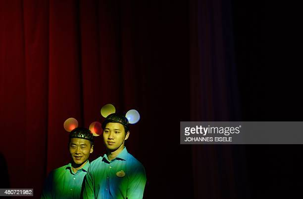 Attendants wearing Mickey Mouse ears stand in front of a red curtain during a press event for the new Shanghai Disney Resort in Shanghai on July 15...