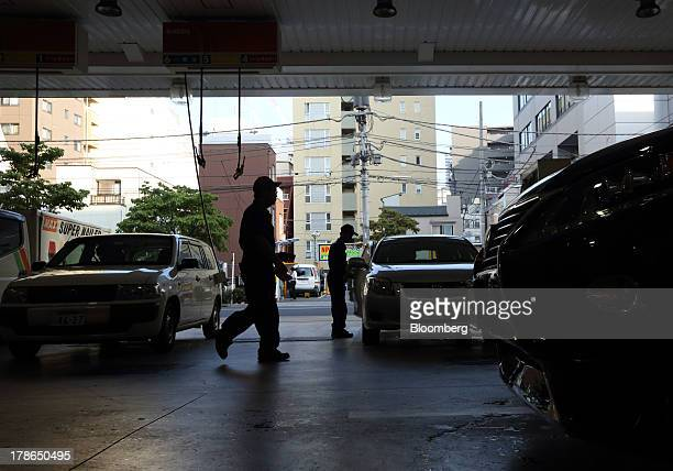 Attendants work as vehicles are refueled at a gas station in Tokyo Japan on Friday Aug 30 2013 Japan's consumer prices increased at the fastest pace...
