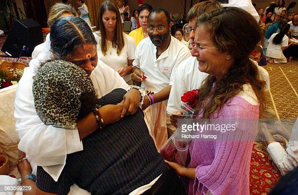 Attendee at right is overcome with emotion while waiting to get a hug from South Indian holy woman Mata Amritanandamayi visit at the LAX Radisson...