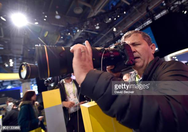Attendee Cezar Vasconcellos examines a Nikon D5 DSLR camera with a 180-400mm zoom lens at the Nikon booth during CES 2018 at the Las Vegas Convention...
