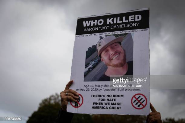 Attendee holds a sign as several hundred members of the Proud Boys and other similar groups gathered for a rally at Delta Park in Portland, Oregon on...