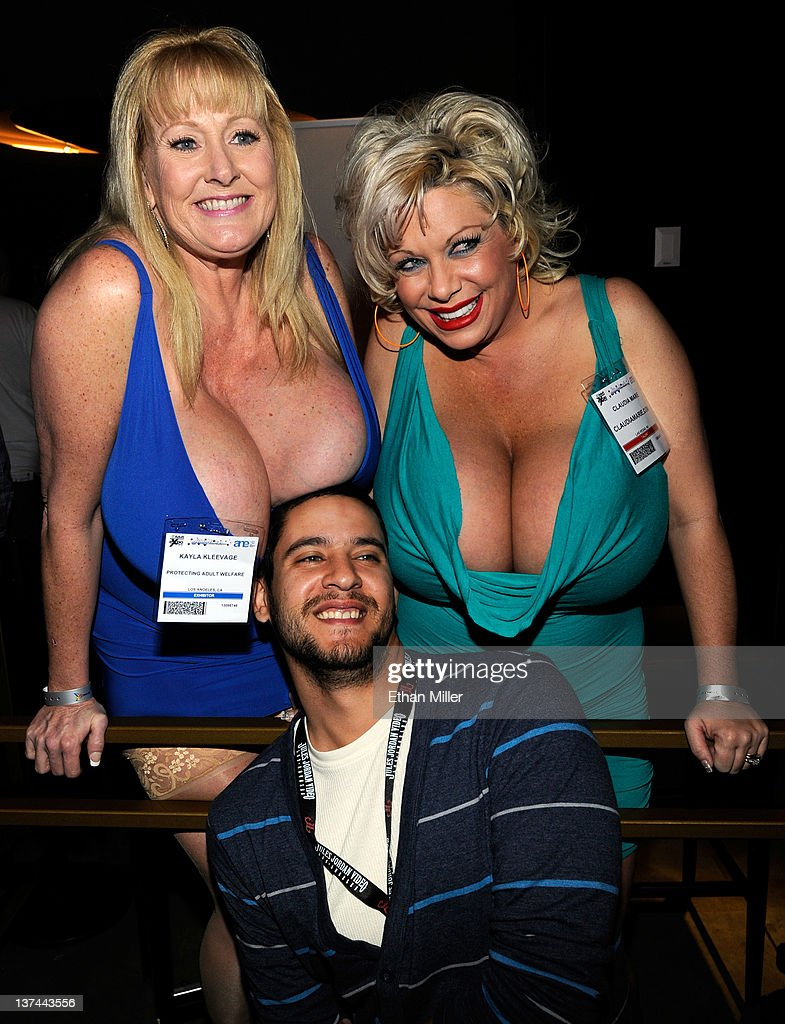 Attendee Louie Batista of New York (C) poses for a photo with adult film actresses and models Kayla Kleevage (L) and Claudia Marie (R) at the 2012 AVN Adult Entertainment Expo at The Joint inside the Hard Rock Hotel & Casino January 20, 2012 in Las Vegas, Nevada.
