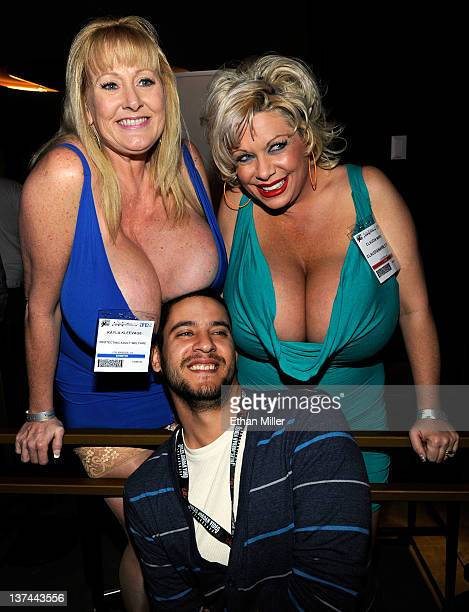 Attendee Louie Batista of New York poses for a photo with adult film actresses and models Kayla Kleevage and Claudia Marie at the 2012 AVN Adult...