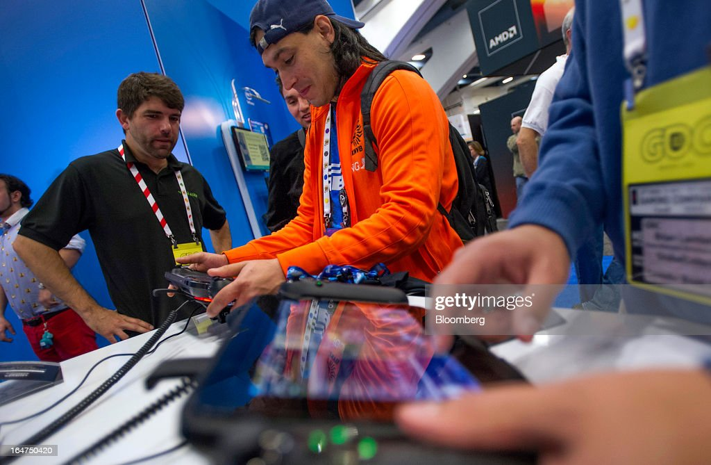 Attendee Miguel Anijel Deloa, center, looks at a game controller at the Intel Corp. booth during the Game Developers Conference 2013 in San Francisco, California, U.S., on Wednesday, March 27, 2013. With over 22,500 attendees, the Game Developers Conference is the world's largest and longest-running professionals-only game industry event. Photographer: David Paul Morris/Bloomberg via Getty Images