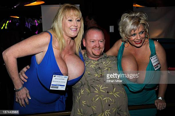 Attendee Robert Ellis of Georgia poses for a photo with adult film actresses and models Kayla Kleevage and Claudia Marie at the 2012 AVN Adult...