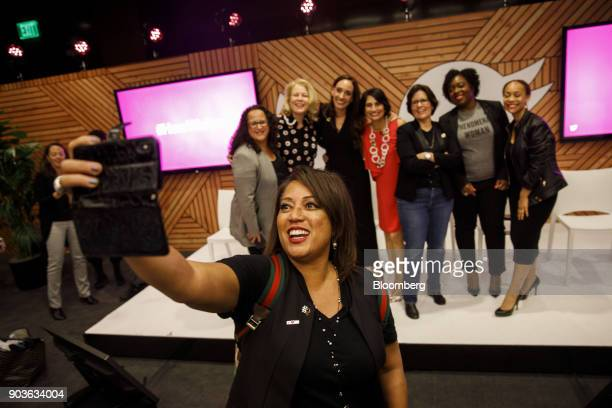 Attendee takes a selfie photograph with Myrna Soto senior vice president of Comcast Corp from left Linda Boff chief marketing officer of General...