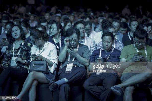 Attendee uses their smartphones ahead of the keynote address at the Huawei Connect 2017 conference in Shanghai China on Tuesday Sept 5 2017 Huawei...