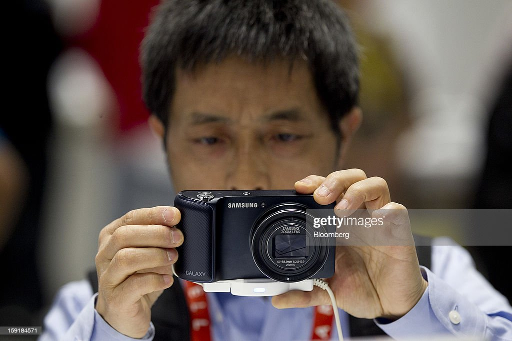 Attendee Yingen Xiong views a Samsung Electronics Co. Galaxy camera during the 2013 Consumer Electronics Show in Las Vegas, Nevada, U.S., on Wednesday, Jan. 9, 2013. Samsung Electronics Co., the world's second-largest semiconductor maker, showed off a speedier and more powerful processor, seeking a bigger stake of the surging smartphone market. Photographer: Andrew Harrer/Bloomberg via Getty Images