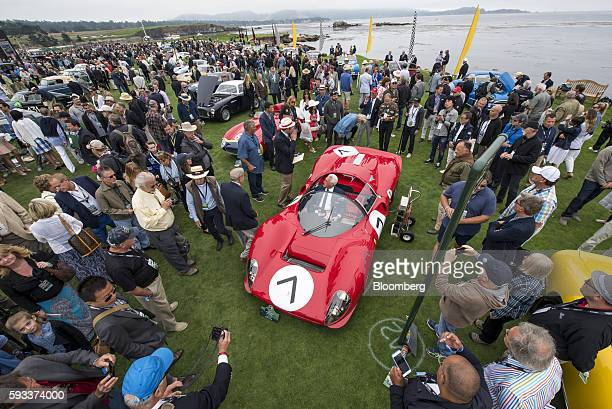 Attendees and judges gather around a 1966 Ferrari 330 P4 Drogo Spyder motor vehicle during the 2016 Pebble Beach Concours d'Elegance in Pebble Beach,...