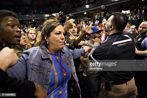 Attendees and security attempt to hold back angry attendees after the cancellation announcement of a campaign event with Donald Trump president and...