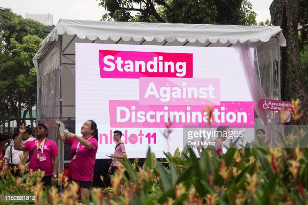 Attendees and volunteers walk past a banner during the Pink Dot event held at the Speaker's Corner in Hong Lim Park on June 29 2019 in Singapore