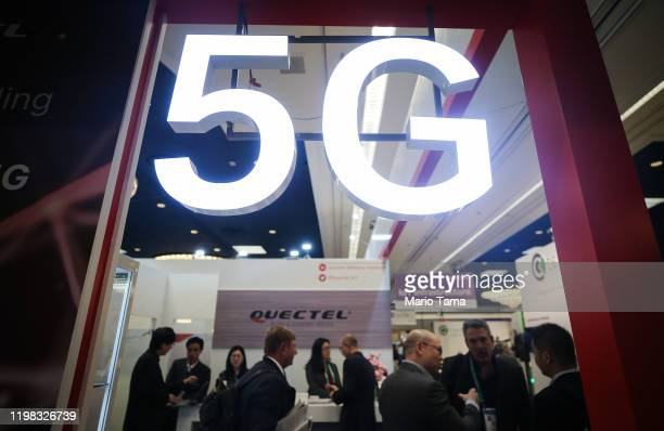 Attendees and workers chat beneath a '5G' logo at the Quectel booth at CES 2020 at the Las Vegas Convention Center on January 8, 2020 in Las Vegas,...