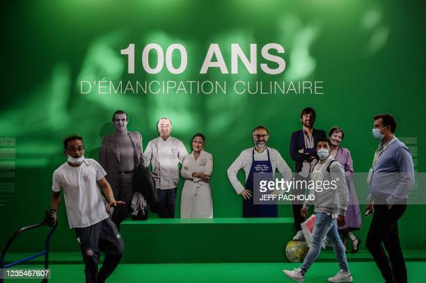 Attendees and workers pass by a placard at the entrance of the SIRHA International Hostel, Restaurant and Food fair in Eurexpo hall in Chassieu, near...