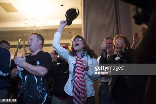 Attendees applaud and cheer while watching polling results during an election night rally with Rick Saccone Republican candidate for the US House of...