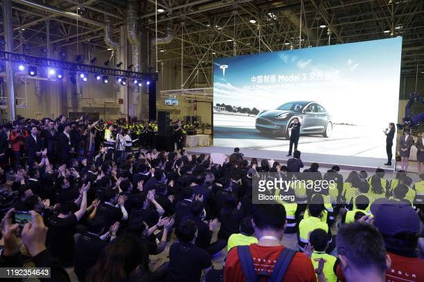 Attendees applaud Elon Musk chief executive officer of Tesla Inc during the Tesla ChinaMade Model 3 Delivery Ceremony at the company's Gigafactory in...